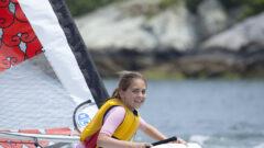 Mädchen mit Schwimmweste segelt mit ihrem Laser BUG fort und schaut zurück